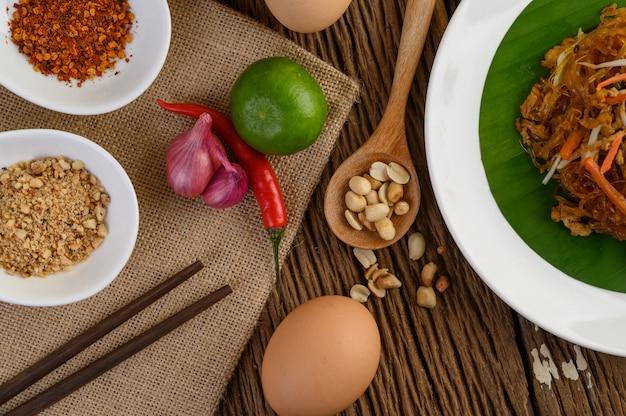 Padthai-garnelen in einer weißen schale mit limette und eiern auf holztisch.