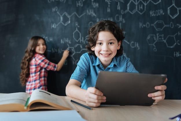 Pädagogische experimente genießen. brainy lächelnd entzückte teenager, die in der schule sitzen und chemieunterricht genießen, während notizen an der tafel machen und tablette verwenden