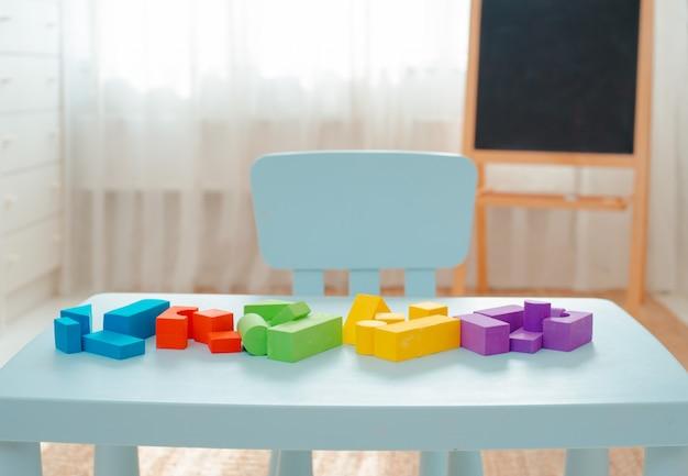 Pädagogische helle geometrische formen, bunte spielwaren auf dem tisch im kinderzimmer