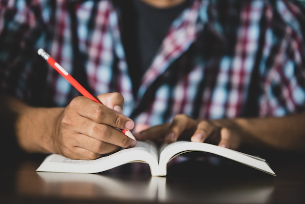 Pädagogisches thema: nahaufnahme student schriftlich in einem klassenzimmer.