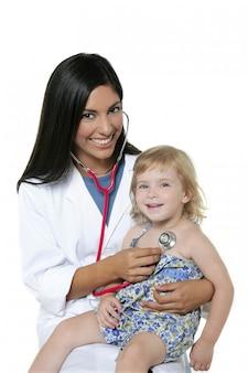 Pädiatrischer doktor des brunette mit blondem kleinem mädchen