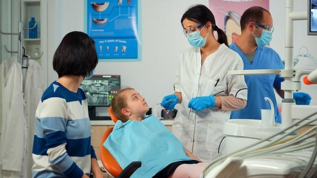 Pädiatrischer stomatologe, der in der nähe eines kleinen mädchenpatienten steht, der stomatologische werkzeuge hält und mit der mutter spricht, bevor er über die betroffene masse spricht. mädchen, das auf stomatologischem stuhl sitzt.