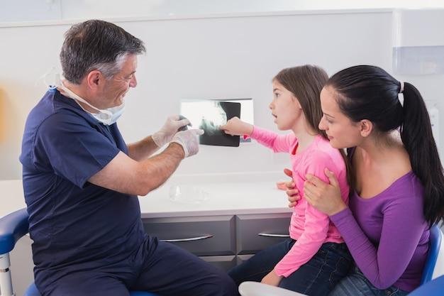 Pädiatrischer zahnarzt, der dem jungen patienten und ihrer mutter den röntgenstrahl erklärt