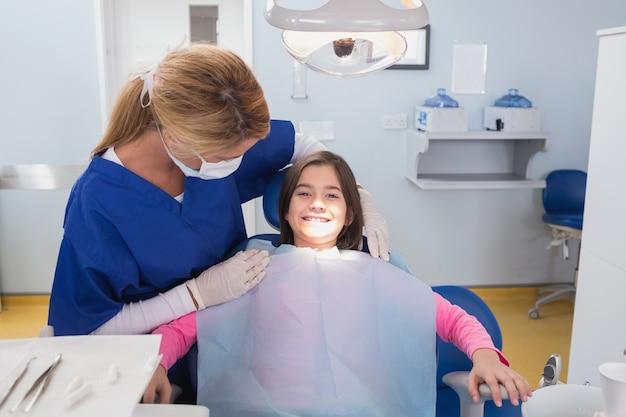 Pädiatrischer zahnarzt, der ihren lächelnden jungen patienten überprüft