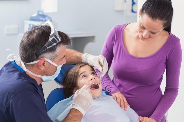 Pädiatrischer zahnarzt, der jungen patienten mit ihrer mutter überprüft