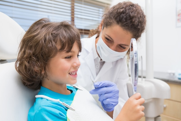 Pädiatrischer zahnarzt, der kleinem jungen seine zähne im spiegel zeigt