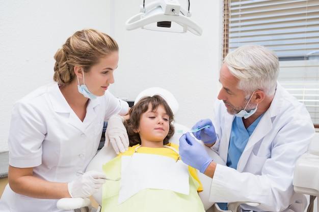 Pädiatrischer zahnarzt, der kleinem jungen zeigt, wie man seine zähne putzt