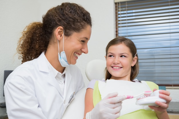 Pädiatrischer zahnarzt, der kleinem mädchen zeigt, wie man ihre zähne putzt