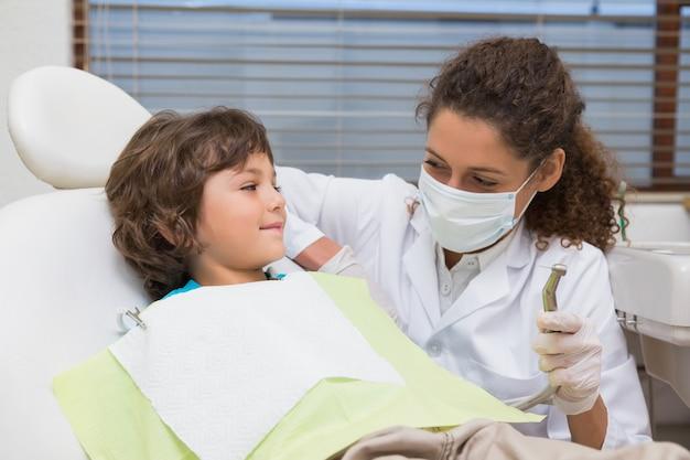 Pädiatrischer zahnarzt, der kleinen jungen im stuhl den bohrgerät zeigt