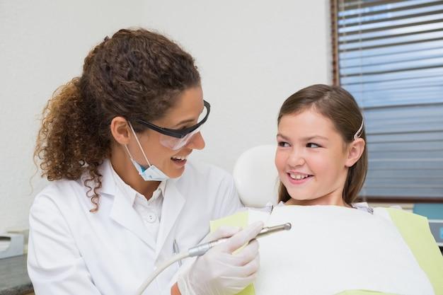 Pädiatrischer zahnarzt, der mit kleinem mädchen im stuhl lächelt