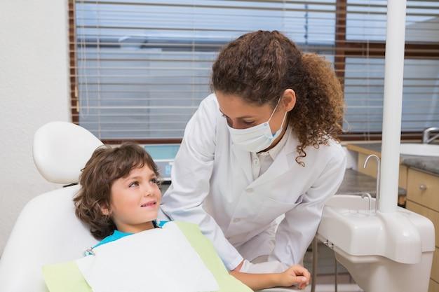 Pädiatrischer zahnarzt, der unten am kleinen jungen im stuhl lächelt