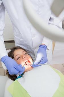 Pädiatrischer zahnarzt, der zähne eines kleinen jungen im zahnarztstuhl überprüft