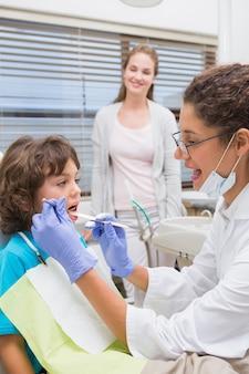 Pädiatrischer zahnarzt, der zähne eines kleinen jungen mit seinem mutteraufpassen überprüft