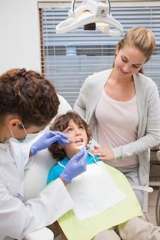 Pädiatrischer zahnarzt, der zähne eines kleinen jungen mit seiner mutter überprüft