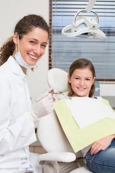 Pädiatrischer zahnarzt und kleines mädchen im zahnarztstuhl, der an der kamera lächelt