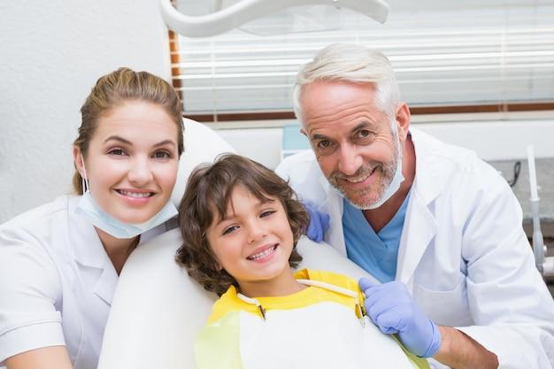 Pädiatrischer zahnarztassistent und kleiner junge, die alle an der kamera lächeln