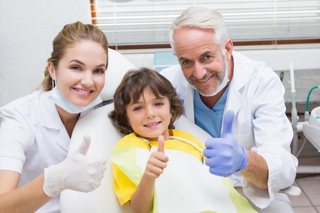 Pädiatrischer zahnarztassistent und kleiner junge, die alle an der kamera mit den daumen oben lächeln