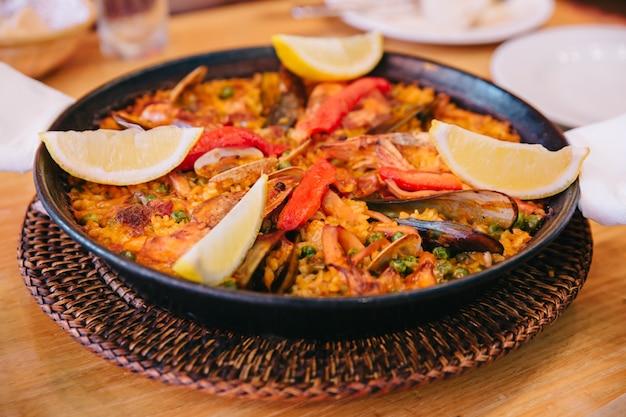 Paella besteht aus kurzkornreis, saubohne, garnelen, perna viridis und venusmuscheln.