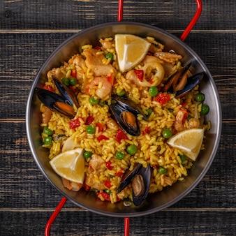 Paella mit hühnchen, meeresfrüchten, gemüse und safran in der traditionellen pfanne.