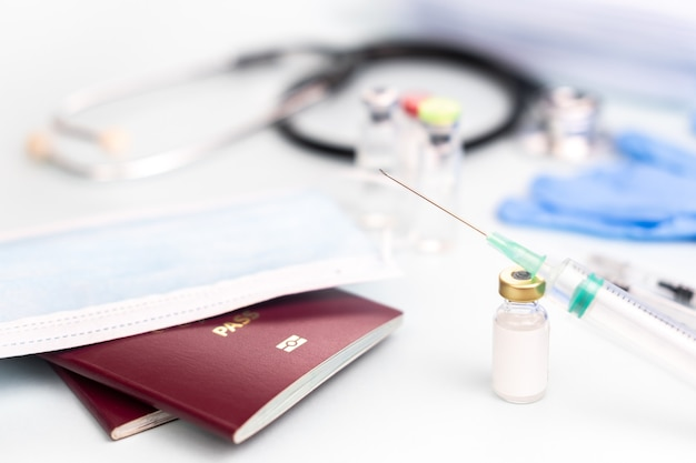 Pässe mit medizinischer maske mit ampullenmodell zur impfung mit verschwommener spritze