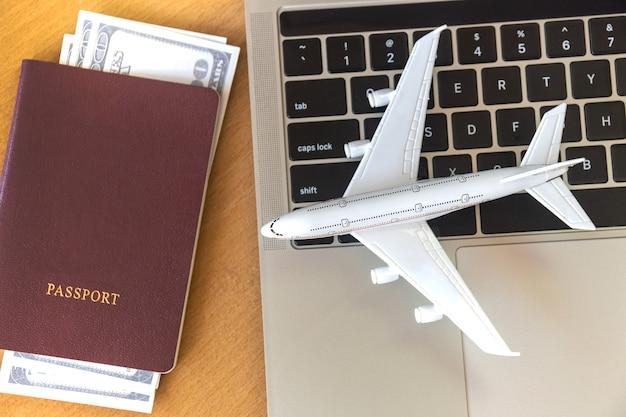 Pässe und geld in der nähe von laptop und flugzeug auf dem tisch. online-ticketbuchungskonzept