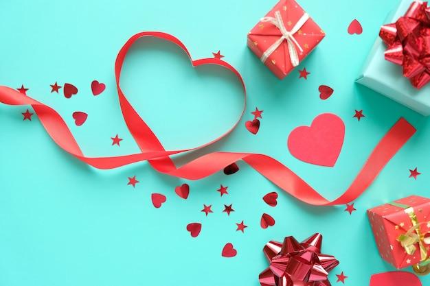 Pailletten in form von herz, geschenken, schleife und rotem glitzer. valentinstag. elemente des roten valentinsgrußes auf neo-minze-hintergrund.