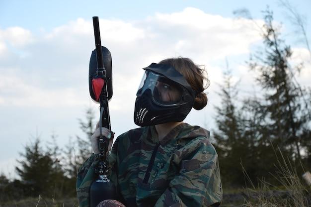 Paintball-sportspieler-mädchen in schützender tarnuniform und maske mit markerpistole im freien