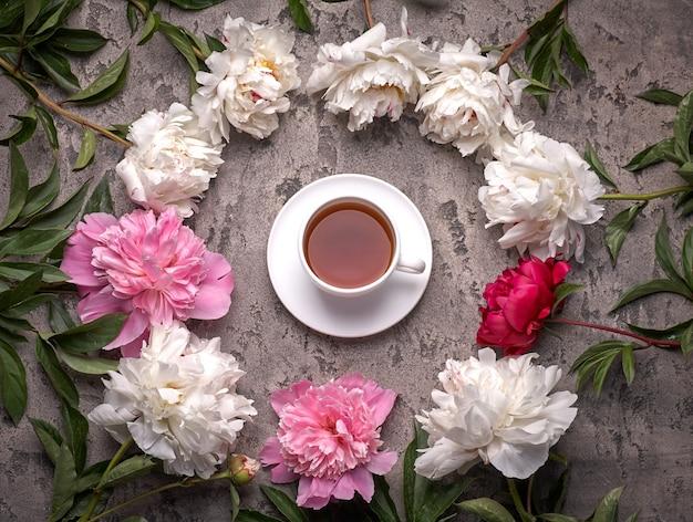 Paionies blumen und tasse kaffee auf grauem hintergrund.
