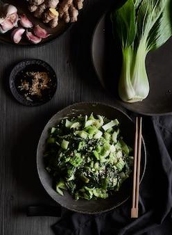 Pak choi stir fry in einem dunklen teller und chinakohl vom tisch