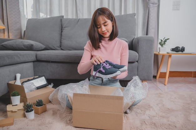 Paket auspacken und paket öffnen beim online-shopping und bei guter lieferung. asiatischer frauenlebensstil im wohnzimmer zu hause. soziale distanzierung und neue normalität.