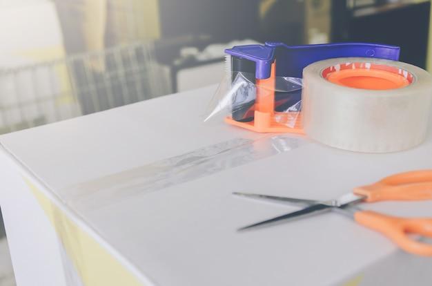 Paket für den versand mit schere und klebebandschneider vorbereiten.