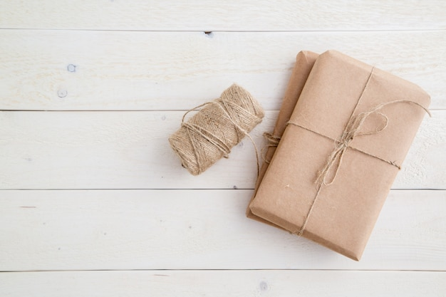Paket, geschenk verpackt im umweltfreundlichen papier und in der schnur für das verpacken auf hellem hölzernem hintergrund. der blick von oben