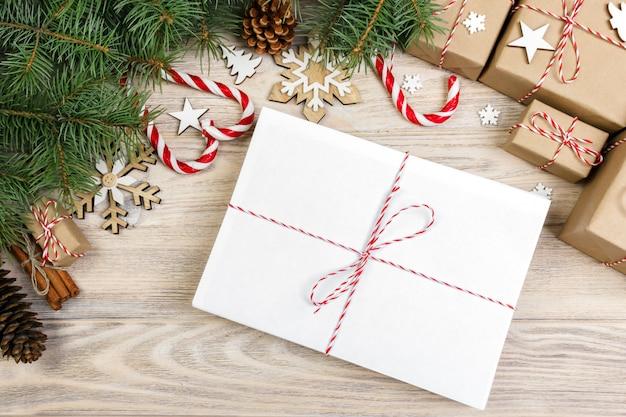 Paket im umschlag mit tannenbaumniederlassungen und weihnachtsdekoration auf einem hölzernen hintergrund