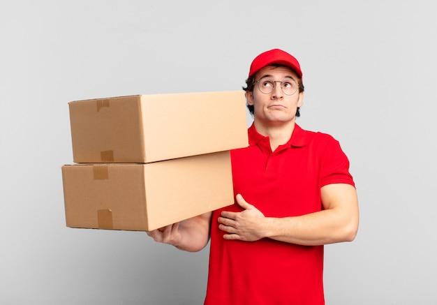 Paket liefern junge achselzuckend, verwirrt und unsicher, zweifelnd mit verschränkten armen und verwirrtem blick