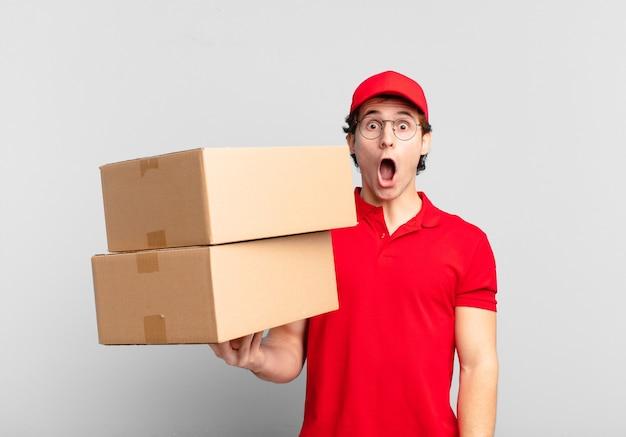 Paket liefern junge, der sehr schockiert oder überrascht aussieht und mit offenem mund anstarrt und sagt wow