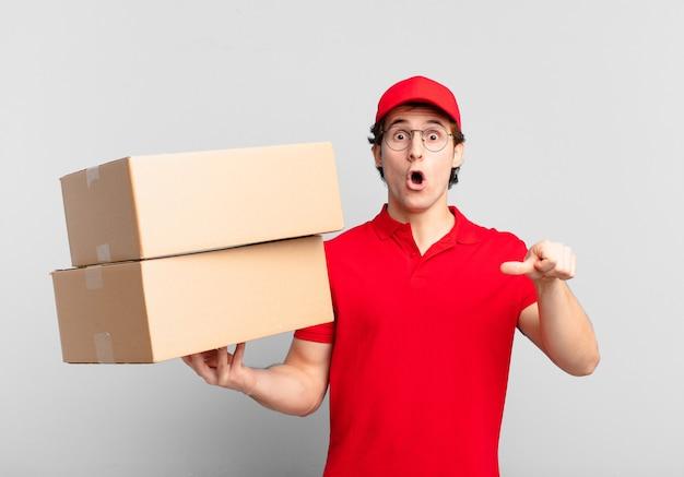 Paket liefern junge, der ungläubig schaut, auf das objekt an der seite zeigt und sagt, wow, unglaublich