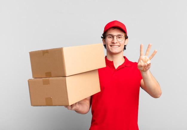 Paket liefern junge lächelnd und freundlich aussehend, nummer drei oder dritte mit der hand nach vorne zeigend, herunterzählen