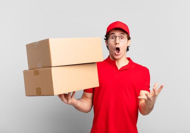 Paket liefern junge mit offenem mund und erstaunt, schockiert und erstaunt mit einer unglaublichen überraschung