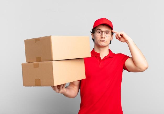 Paket liefern jungen, die sich verwirrt und verwirrt fühlen und zeigen, dass sie verrückt, verrückt oder verrückt sind