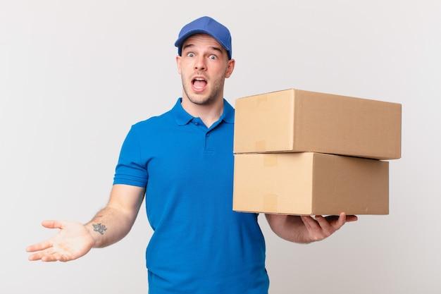 Paket liefern mann, der sehr schockiert oder überrascht aussieht und mit offenem mund anstarrt und sagt wow