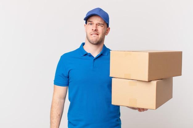 Paket liefern mann, der verwirrt und verwirrt aussieht, sich mit einer nervösen geste auf die lippe beißt und die antwort auf das problem nicht kennt