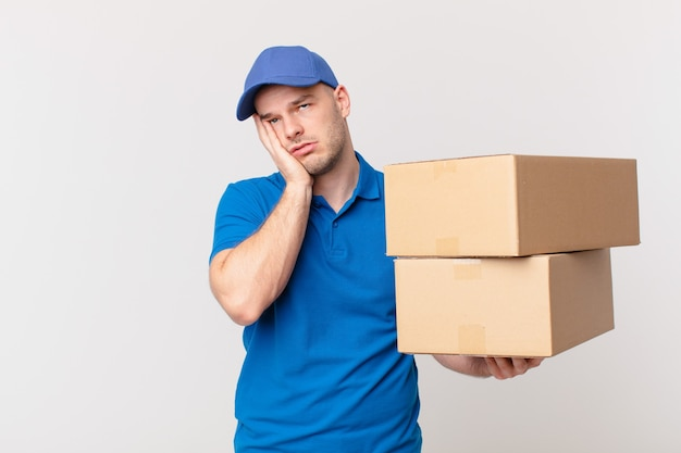 Paket liefert mann, der sich nach einer ermüdenden, langweiligen und langweiligen aufgabe gelangweilt, frustriert und schläfrig fühlt und das gesicht mit der hand hält