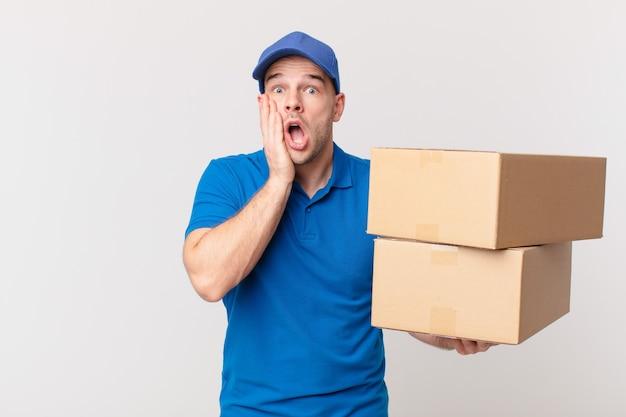 Paket liefert mann, der sich schockiert und verängstigt fühlt und mit offenem mund und händen auf den wangen verängstigt aussieht