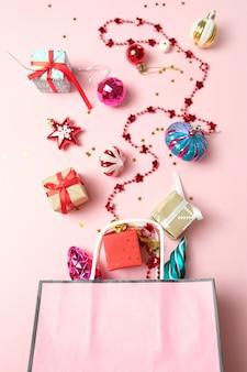 Paket mit unterschiedlicher weihnachtsdekoration auf rosa