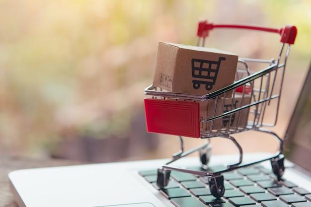 Paket- oder papierkartons mit einem einkaufswagenlogo in einem wagen auf laptop-tastatur. einkaufsservice im online-web. bietet lieferung nach hause.