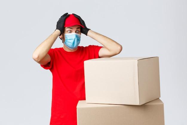 Paket- und paketzustellung, covid-19-quarantäne und überweisungsaufträge. besorgter und besorgter kurier in roter uniform, gesichtsmaske und handschuhen, schnappt sich den kopf und starrt schockiert auf kisten