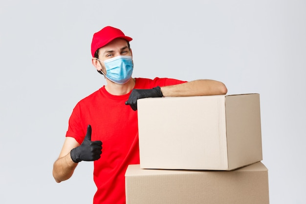 Paket- und paketzustellung, covid-19-quarantäne und überweisungsaufträge. zuversichtlicher kurier in roter uniform, handschuhen und medizinischer maske, anrufservice fördern, daumen nach oben auf kisten lehnen