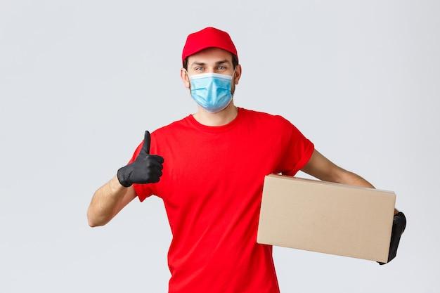Paket- und paketzustellung, covid-19-quarantänezustellung, überweisungsaufträge. fröhlicher kurier in roter uniform, handschuhe und mundschutz, daumen hoch, kontaktlose lieferung empfehlen, karton mit bestellung halten