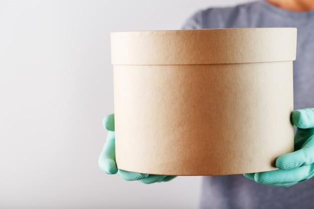 Paket von einem lieferservice kurier mit gummihandschuhen und einer maske.