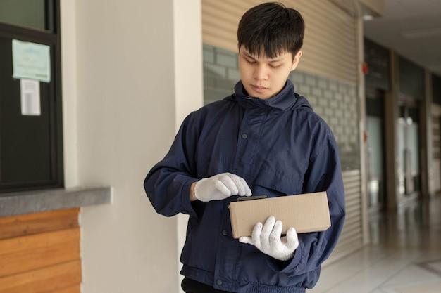 Paketzustellungskonzept der junge postbote im marineblauen mantel sucht mit seinem smartphone nach der adresse seines kunden, um das paket zu versenden.